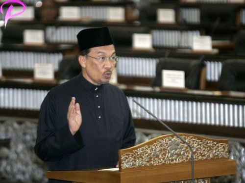 Malaysia's leading opposition figure Anwar Ibrahim raises his hand as he is sworn in as a member of parliament at the parliament house in Kuala Lumpur, August 28, 2008. Anwar won a sweeping victory in a by-election on Tuesday and returns to parliament just in time to join Friday's 2009 budget announcement and debate.