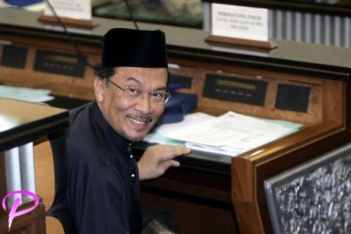 Malaysia's opposition figure Anwar Ibrahim acknowledges journalists as he sits after being sworn in as a member of parliament at the parliament house in Kuala Lumpur, August 28, 2008. Anwar won a sweeping victory in a by-election on Tuesday and returns to parliament just in time to join Friday's 2009 budget announcement and debate.