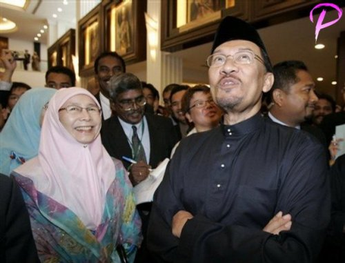 Malaysian opposition leader Anwar Ibrahim, right, and his wife Wan Azizah arrive at Parliament house in Kuala Lumpur, Malaysia, Thursday, Aug. 28, 2008. Anwar took his place Thursday as a member of Malaysia's Parliament, a major step in his goal to topple the government weakened by electoral defeats and internal dissent.