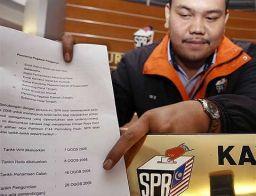 UMUM ... Kakitangan Suruhanjaya Pilihan Raya (SPR) Iskandar Abdul Wahab,26, menunjukkan tarikh pilihanraya bagi kawasan Parlimen Permatang Pauh yang telah ditetapkan di lobi ibu pejabat SPR di sini, hari ini.