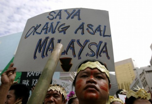 "An indigenous Malaysian holds a placard saying ""I am an original inhabitant of Malaysia"" during a demonstration to call for the government to implement the individual and collective rights of indigenous people, in Kuala Lumpur September 13, 2008."