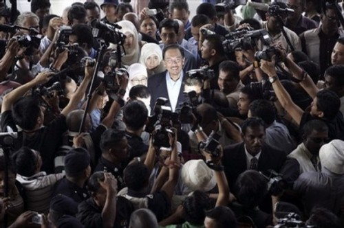 Malaysian opposition leader Anwar Ibrahim, center, is surrounded as he arrives at a court house in Kuala Lumpur, Malaysia, Wednesday, Sept. 10, 2008. (AP Photo/Lai Seng Sin)