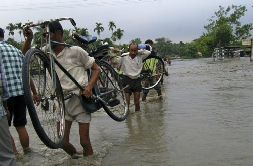 People carry their belongings as they wade through a flooded road in Puthimari village, 80 km (50 miles) west of the eastern Indian city of Guwahati, September 2, 2008. Heavy rains and rising floodwaters forced hundreds of thousands of people from their homes in northeastern India and sent elephants and rhinos fleeing, as monsoon misery spread in South Asia.