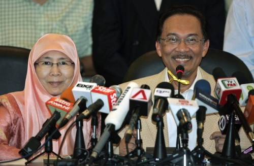 Malaysia's opposition leader Anwar Ibrahim speaks as wife Wan Azizah Wan Ismail smiles during a news conference at their office in Petaling Jaya outside Kuala Lumpur September 16, 2008. Malaysia's opposition alliance has enough support from MPs to oust the government and wants to meet with the country's premier to plan a handover, leader Anwar Ibrahim said on Tuesday.