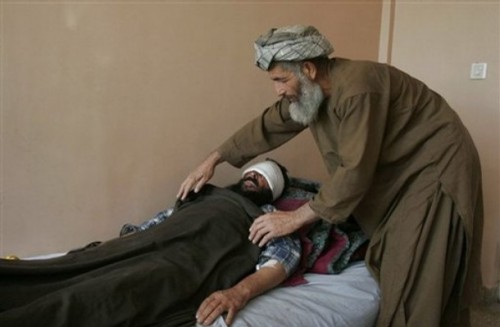 An unidentified relative puts a sheet over Sayed Ghulam, an Afghan farmer, after an interview with The Associated Press at a hospital in the city of Kandahar, south of Kabul, Afghanistan, Sunday, Oct. 26, 2008. Ghulam said armed assailants attacked him and gouged out his eyes in front of his family in an attack in southern Afghanistan, officials said Sunday.