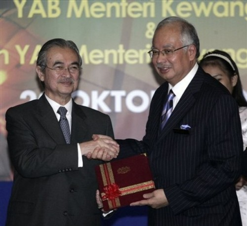 Malaysian Prime Minister Abdullah Ahmad Badawi, left, shakes hands as he hands over his finance minister's post to his deputy Najib Razak, right, in Putrajaya, Malaysia, Monday, Oct. 20, 2008. Malaysia announced plans Monday to prop up the stock market and lure more foreign investment amid expectations of slower economic growth next year.