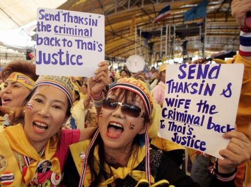 Supporters of the People's Alliance for Democracy (PAD) cerebrate and hold a banner at the Government House in Bangkok on October 21, 2008. Thailand's Supreme Court ruled on Tuesday that former prime minister Thaksin Shinawatra had violated a conflict-of-interest law while in office and sentenced him to two years in prison.