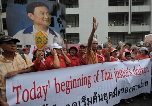 Supporters of ousted premier Thaksin Shinawatra hold his portrait while shouting slogans during a demonstration at the Supreme Court in Bangkok on October 21, 2008. Thailand's Supreme Court found ousted premier Thaksin Shinawatra guilty of conflict of interest in connection with a land deal for his wife and sentenced him in absentia to two years in prison.