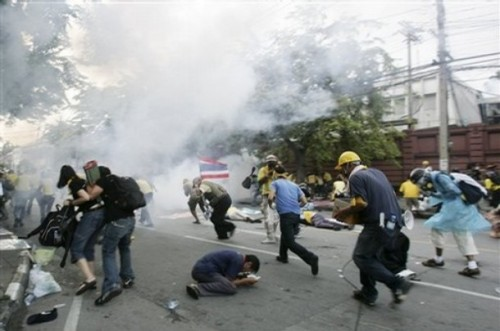 Anti-government protesters flee from tear gas smoke in front of parliament in Bangkok, Thailand, on Tuesday, Oct. 7, 2008. Police fired tear gas Tuesday at several thousand demonstrators attempting to block access by lawmakers to the Parliament building in the Thai capital.