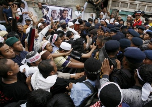 Indonesian hardliner Muslims clash with policemen as the dead bodies of Bali bombers Amrozi and Muklas alias Ali Gufron arrive at Tenggulun village near Lamongan, East Java province November 9, 2008. Thousands of people including some hardliners gathered for the funerals of three Indonesians executed on Sunday for the 2002 Bali bombings, sparking clashes between police and emotional supporters. REUTERS/Beawiharta (INDONESIA)