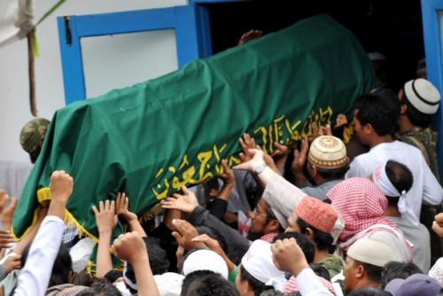 "Supporters carry a coffin containing either Mukhlas or Amrozi (unclear) as they arrive at Al Islam boarding school in Tenggulun on November 9, 2008.  Grief and religious fervour boiled over into calls for revenge here as two brothers executed for their role in the 2002 Bali attacks were buried amid tight security.   A crowd of about 500 supporters briefly clashed with police near the family home of 47-year-old Amrozi -- dubbed the ""smiling assassin"" for his disturbing grin -- and Mukhlas, 48, as their bodies arrived in their east Java village. AFP PHOTO/ADEK BERRY (Photo credit should read ADEK BERRY/AFP/Getty Images)"