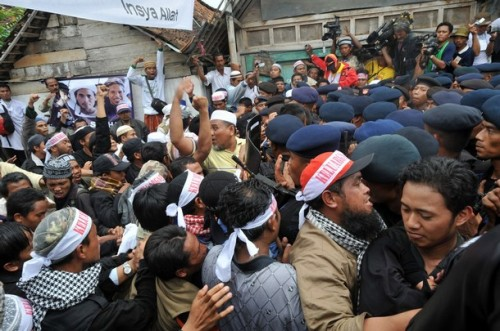 "Indonesian Mobile Brigade Policemen clash with supporters shortly before the funeral of the bodies of Amrozi and Mukhlas in Tenggulun on November 9, 2008. Grief and religious fervour boiled over into calls for revenge here as two brothers executed for their role in the 2002 Bali attacks were buried amid tight security.   A crowd of about 500 supporters briefly clashed with police near the family home of 47-year-old Amrozi -- dubbed the ""smiling assassin"" for his disturbing grin -- and Mukhlas, 48, as their bodies arrived in their east Java village. AFP PHOTO/ADEK BERRY (Photo credit should read ADEK BERRY/AFP/Getty Images)"
