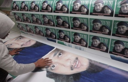 """A worker monitors prints of posters of Bali bomber Imam Samudra with his daughter at a printing shop owned by Samudra's relative in Banten, West Java November 6, 2008. The attorney general's office has said the three militants-- Imam Samudra, Mukhlas and Amrozi--would be executed in early November for their role in the 2002 nightclub bombings on the resort island in which 202 people died. The writing on the posters read, """"Mujahideen, fight""""."""