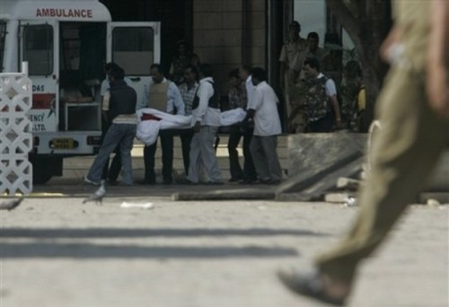 Rescue and security personnel carry a body from the Taj Hotel in Mumbai, India, Thursday, Nov. 27, 2008. Teams of gunmen stormed luxury hotels, a popular restaurant, hospitals and a crowded train station in coordinated attacks across India's financial capital, killing at least 101 people, taking Westerners hostage and leaving parts of the city under siege Thursday, police said. A group of suspected Muslim militants claimed responsibility. (AP Photo/Rajanish Kakade)