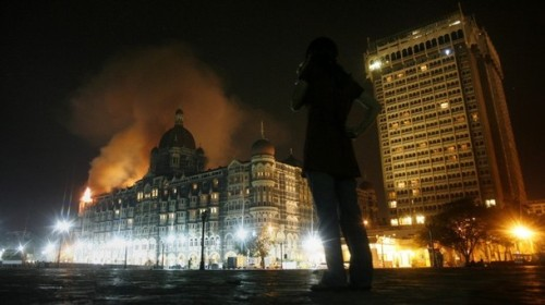 A reporter talks on her phone as smoke is seen coming from Taj Hotel in Mumbai November 27, 2008. Large plumes of smoke were seen rising from the top of the landmark Taj Hotel in Mumbai on Thursday and heavy firing could be heard, a Reuters witness said. Local TV reported that unknown assailants had earlier attacked the hotel, taking hostages, including Western tourists.  REUTERS/Arko Datta (INDIA)