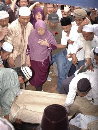 Emby Badriyah, center, looks on the coffin of her son, Bali bomber Imam Samudra, arrive at a cemetery in Serang, Banten province, Indonesia, Sunday Nov. 9, 2008. Indonesia executed Samudra, 38, and brothers Amrozi Nurhasyim, 47, and Ali Ghufron, 48, Saturday for helping plan and carry out the 2002 Bali bombings that killed 202 people, many of them foreign tourists. (AP Photo)