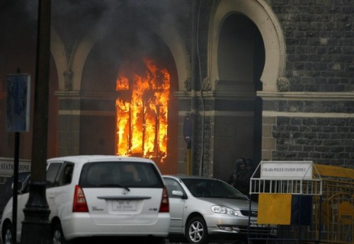 A portion of Taj Mahal hotel is set ablaze during a gun battle as Indian soldiers look on in Mumbai November 29, 2008. Operations to dislodge militants at the Taj Mahal hotel in Mumbai ended on Saturday, security officials said, and at least three Islamist gunmen were killed.REUTERS/Arko Datta (INDIA)