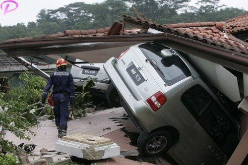 A rescuer inspects a residence damaged by a landslide in Kuala Lumpur December 6, 2008. A landslide occurred early Saturday in a housing estate in Kuala Lumpur and police confirmed three people killed, according to Malaysia's official Bernama news agency.