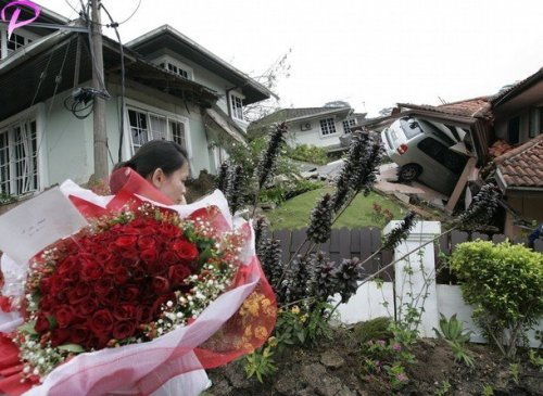 A woman delivers a bouquet of flowers to a residence damaged by a landslide in Kuala Lumpur December 6, 2008. A landslide occurred early Saturday in a housing estate in Kuala Lumpur and police confirmed three people killed, according to Malaysia's official Bernama news agency.Reuters Pictures
