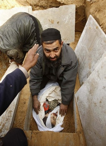 A Palestinian man buries the body of 5-year-old Sodqi al-Absi in Rafah cemetery in the southern Gaza Strip December 29, 2008. Palestinian medics said five young sisters died in an air strike in Jabalya refugee camp in northern Gaza and three other young children one of them al-Absi, were killed when a bomb struck a house aimed at the nearby abandoned home of a senior Hamas militant in Rafah.  REUTERS/Ibraheem Abu Mustafa (GAZA)