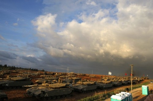 Israeli soldiers stands near tanks at a staging area just outside the northern Gaza Strip December 29, 2008. Israeli aircraft destroyed a bastion of Hamas's rule over the Gaza Strip on Monday, the third day of an offensive that has killed more than 300 Palestinians in the deadliest violence in the territory in decades.  REUTERS/Baz Ratner (ISRAEL)