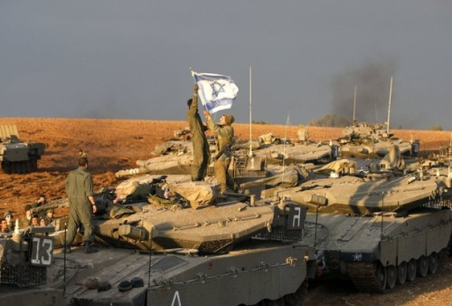Israeli soldiers hang a national flag on the antenna of their tank at a staging area just outside the northern Gaza Strip December 29, 2008. Israeli aircraft destroyed a bastion of Hamas's rule over the Gaza Strip on Monday, the third day of an offensive that has killed more than 300 Palestinians in the deadliest violence in the territory in decades.  REUTERS/Baz Ratner (ISRAEL)