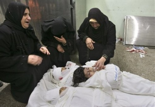 Palestinian women mourn over the bodies of three Palestinian children from the Balosha family, of five who were all killed in the same Israeli missile strike,  in the morgue before their burial at Kamal Edwan hopsital in Beit Lahiya, northern Gaza Strip, Monday, Dec. 29, 2008. Israel's overwhelming air campaign against the Gaza Strip inched closer to the territory's Hamas rulers as the assault entered its third day Monday, as missiles struck a house next to the Hamas premier's home and destroyed symbols of the Islamic movement's power. (AP Photo/Eyad Baba)