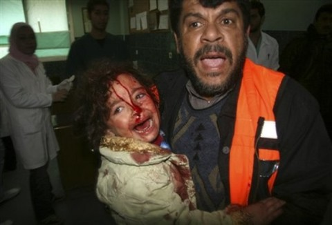 A Palestinian medic carries a wounded girl to the treatment room of Shifa hospital following an Israeli missile strike in Gaza City, Thursday, Jan. 1, 2009. More than 400 Gazans have been killed and some 1,700 have been wounded since Israel embarked on its aerial campaign, Gaza health officials said. (AP Photo/Ashraf Amra)