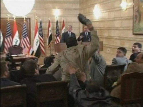 In this image from APTN video, a man, centre throws a shoe at US President George W. Bush, background left, during a news conference with Iraq Prime Minister Nouri al-Maliki, Sunday, Dec. 14, 2008, in Baghdad, Iraq. On an Iraq trip shrouded in secrecy and marred by dissent, President George W. Bush on Sunday hailed progress in the war that defines his presidency and got a size-10 reminder of his unpopularity when a man hurled two shoes at him during a news conference. (AP Photo)