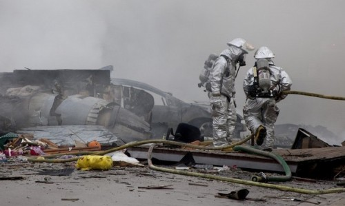 Firefighters look near the remains of a military jet that crashed into homes in the University City neighborhood of San Diego, California December 8, 2008. REUTERS