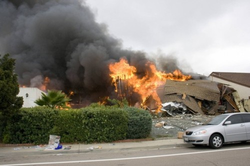 Flames engulf a home in the University City neighborhood after a military jet crashed into homes in San Diego, California December 8, 2008. The jet crashed into the California neighborhood near San Diego on Monday after the pilot ejected, killing two people on the ground and destroying two homes, officials said.  REUTERS