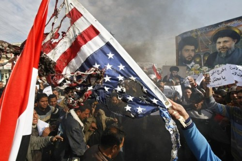 Iraqis burn the replica of the US flag during a protest against yesterday's visit by US President George W. Bush and the arrest of an Iraqi journalist in the eastern Baghdad district of Sadr City on December 15, 2008. An Iraqi television station, Al-Baghdadia channel which broadcasts from Cairo, today demanded the immediate release of one of its journalists Muntazer al-Zaidi who caused a furore when he hurled shoes at visiting US President George W. Bush last night during a joint press conference with Iraqi Premier Nuri al-Maliki in Baghdad. Bush was on a surprise farewell visit to Iraq. Poster in the background depicts the images of  anti-US Shiite Muslim cleric Moqtada Sadr (L) and Ayatollah Mohammed Baqr al-Sadr, assassinated during the regime of ousted President Saddam Hussein on April 9,1980. AFP PHOTO / AHMAD AL-RUBAYE (Photo credit should read AHMAD AL-RUBAYE/AFP/Getty Images)