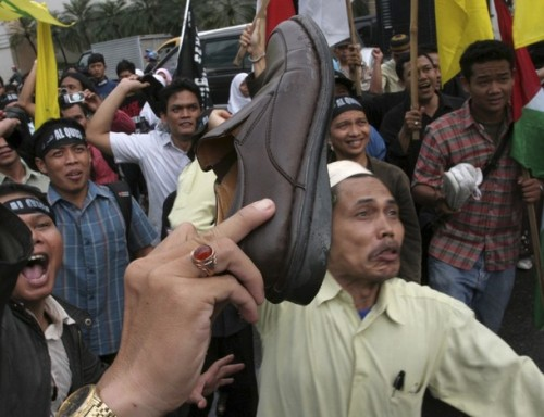 Muslim activists shows their shoes during a protest in front of the U.S. consulate in Medan, North Sumatra province, December 19, 2008. Dozens of activists gathered in protest to demand the release of Iraqi TV reporter Muntazer al-Zaidi, who threw his shoes at U.S. President George W. Bush during a recent news conference in Iraq, from jail. REUTERS/YT Haryono (INDONESIA)