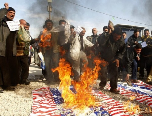 Demonstrators burn mock U.S. flags during a protest demanding the release of Iraqi TV reporter Muntazer al-Zaidi from detention, in Baghdad's Sadr City December 19, 2008. Zaidi, who threw his shoes at U.S. President George W. Bush apologized to Iraqi Prime Minister Nuri al-Maliki for embarrassing him before the watching world, the prime minister's office said on Thursday.   REUTERS/Thaier al-Sudani