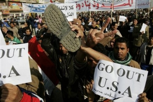 A shoe is raised during a protest against the US President's visit in the Shiite stronghold of Sadr City in Baghdad, Iraq, Monday. Dec. 15, 2008.  Iraqi journalist Muntadar al-Zeidi threw his shoes at President George W. Bush during a press conference in Baghdad on Sunday, while yelling in Arabic.(AP Photo/Karim Kadim)