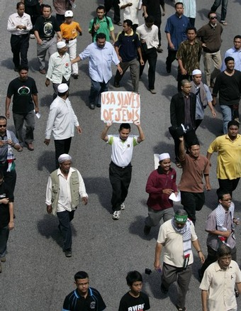 A Muslim demonstrator holds up a placard during a demonstration in protest of Israeli aggression against Palestinians, in Kuala Lumpur December 30, 2008. REUTERS/Bazuki Muhammad (MALAYSIA)