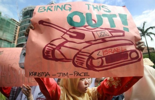 "Malaysian protesters from the Malaysian Islamic Party (PAS) hold banners and shout slogans during a rally against the recent Israeli military attacks on Gaza, outside the US embassy in Kuala Lumpur on December 30, 2008. Warplanes pounded Gaza for a fourth day as tanks stood by to join the ""all-out"" war Israel vowed would wipe out Hamas, and the Palestinian death toll rose to at least 360. Israel made it clear on December 29 the offensive was just beginning, even as UN chief Ban Ki-moon urged world leaders to work urgently to end the ""unacceptable"" violence. AFP PHOTO (Photo credit should read AFP/AFP/Getty Images)"