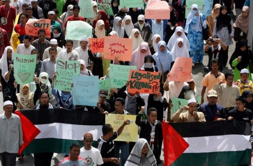 Malaysian protesters hold placards and Palestine flags during a rally against Israeli military attacks on Gaza, outside the US embassy in Kuala Lumpur on December 30, 2008. More than 500 protesters from Malaysian Islamic Party (PAS) held a rallied after Israeli warplanes and combat helicopters pounded the Hamas-ruled Gaza Strip on December 29, killing at least 155 people in the bloodiest day for Palestinians in more than 20 years. AFP PHOTO  (Photo credit should read AFP/AFP/Getty Images)