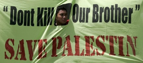 A Muslim demonstrator holds a banner during a demonstration in protest of Israeli aggression against Palestinians, in Kuala Lumpur December 30, 2008. REUTERS/Bazuki Muhammad (MALAYSIA)