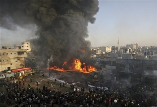 Black smoke rises from a burning building as Palestinians gather at the site of an Israeli missile strike in the Rafah refugee camp, southern Gaza Strip, Sunday, Dec. 28, 2008. Israeli warplanes pressing one of Israel's deadliest assaults ever on Palestinian militants dropped bombs and missiles on a top security installation and dozens of other targets across Hamas-ruled Gaza on Sunday. Israel's Cabinet authorized a callup of at least 6,500 reserve soldiers, suggesting plans to expand an offensive against Gaza rocket squads that has already killed some 280 Palestinians. (AP Photo/Eyad Baba)