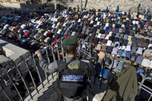 An Israeli border police officer stands guard as Palestinians pray in the street after being prevented by from entering the Al Aqsa Mosque compound, also known to Jews as the Temple Mount, for Friday prayers in Jerusalem's Old City, Dec. 5, 2008. Israel placed military and police forces on alert Friday to head off new violence after the evacuation of a disputed West Bank building brought tensions between the government, extremist settlers and Palestinians to a peak.