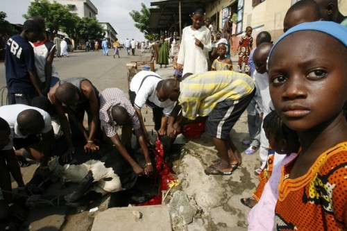 Muslims slaughter sheep on the street in Attiecoube, Abidjan December 8, 2008. Muslims around the world celebrate Eid al-Adha by slaughtering sheep, goats, camels and cows to commemorate Prophet Abraham's willingness to sacrifice his son, Ismail, on God's command.REUTERS