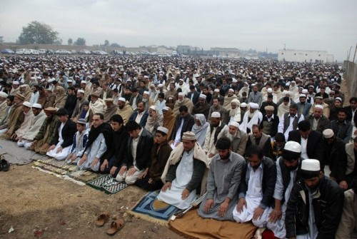Afghan refugees living in Peshawar offer prayers to celebrate Eid al-Adha December 8, 2008. Muslims around the world celebrate Eid al-Adha to mark the end of the haj by slaughtering sheep, goats, cows and camels to commemorate Prophet Abraham's willingness to sacrifice his son Ismail on God's command.   REUTERS