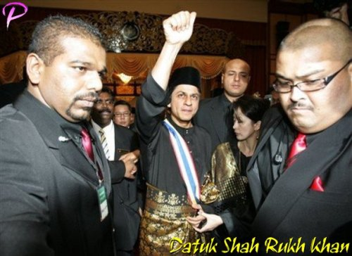 """Bollywood actor Shah Rukh Khan in a traditional official black Malay costume and songkok cap, center, waves after he received the title of """"Datuk"""" from Malacca state Governor Mohammad Khalil Yaakob in Malacca, 148 km south of Kuala Lumpur, Malaysia, Saturday, Dec. 6, 2008.  Bollywood heartthrob Shah Rukh Khan was conferred a Malaysian honorary title equivalent to a British knighthood despite claims by some Malaysians that it is wrong to honor a foreigner. (AP Photo/Lai Seng Sin)"""