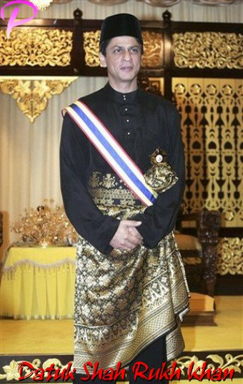 """Bollywood actor Shah Rukh Khan in a traditional official black Malay costume and songkok cap poses after he received the title of """"Datuk"""" from Malacca state Governor Mohammad Khalil Yaakob in Malacca, 148 km south of Kuala Lumpur, Malaysia, Saturday, Dec. 6, 2008.  Bollywood heartthrob Shah Rukh Khan was conferred a Malaysian honorary title equivalent to a British knighthood despite claims by some Malaysians that it is wrong to honor a foreigner. (AP Photo/Lai Seng Sin)"""