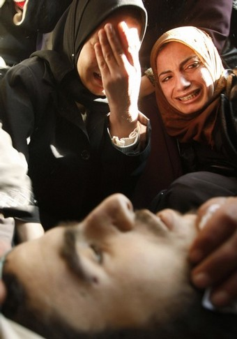 Palestinian relatives of Hamas militant Mohammed Abu Shair, who was killed by an Israeli air strike, mourn beside his body during his funeral in Rafah in the southern Gaza Strip January 5, 2009. Israeli tanks, planes and ground forces pounded Gaza on Monday and the defence minister said the offensive against Hamas militants in the Palestinian enclave would go on until Israel was safe. REUTERS/Ibraheem Abu Mustafa (GAZA)