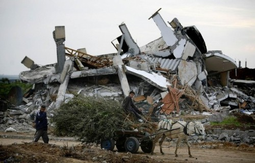 A Palestinian boy rides a donkey-pulled cart past a destroyed house on the outskirts of Jabalya in the northern Gaza Strip January 19, 2009. More Israeli forces left the Gaza Strip on Monday after a 22-day assault on Hamas militants, and both sides kept a ceasefire, allowing dazed Palestinians to survey the destruction and mourn their dead.  REUTERS/Jerry Lampen (GAZA)