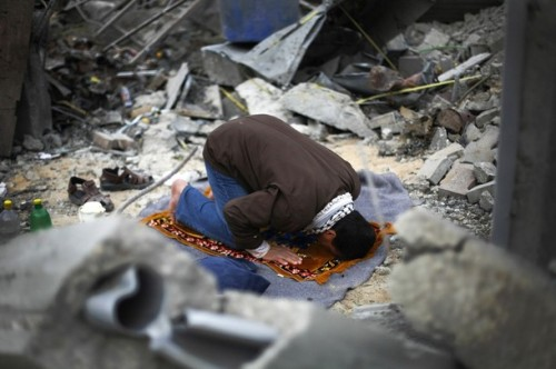 A Palestinian man prays in the rubble of his house in Beit Lahiya, in the northern Gaza Strip January 19, 2009. More Israeli forces left the Gaza Strip on Monday after a 22-day assault on Hamas militants, and both sides kept a ceasefire, allowing dazed Palestinians to survey the destruction and mourn their dead. REUTERS/Anja Niedringhaus/Pool  (GAZA)