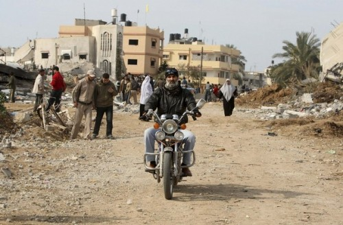 A Palestinian rides a motorcycle past houses destroyed during Israel's offensive in Jabalya in the northern Gaza Strip January 19, 2009. Israeli forces were pulling out of the Gaza Strip on Monday following a tentative truce with Hamas that allowed Palestinians to take stock of the devastating three-week war.  REUTERS/Suhaib Salem (GAZA)