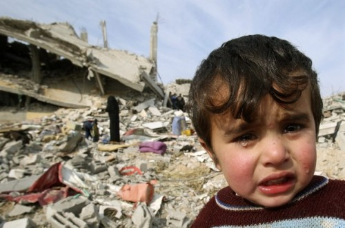 A Palestinian boy stands next to his family's house, destroyed during Israel's offensive, in Jabalya in the northern Gaza Strip January 19, 2009. Israeli forces were pulling out of the Gaza Strip on Monday following a tentative truce with Hamas that allowed Palestinians to take stock of the devastating three-week war. REUTERS/Suhaib Salem (GAZA)